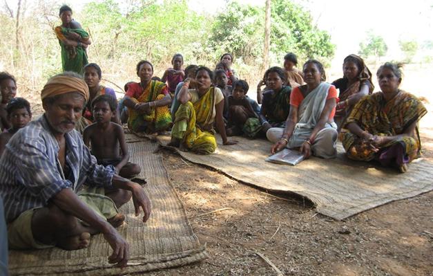 Dorfbewohner sitzen in zwei Gruppen auf dem Boden
