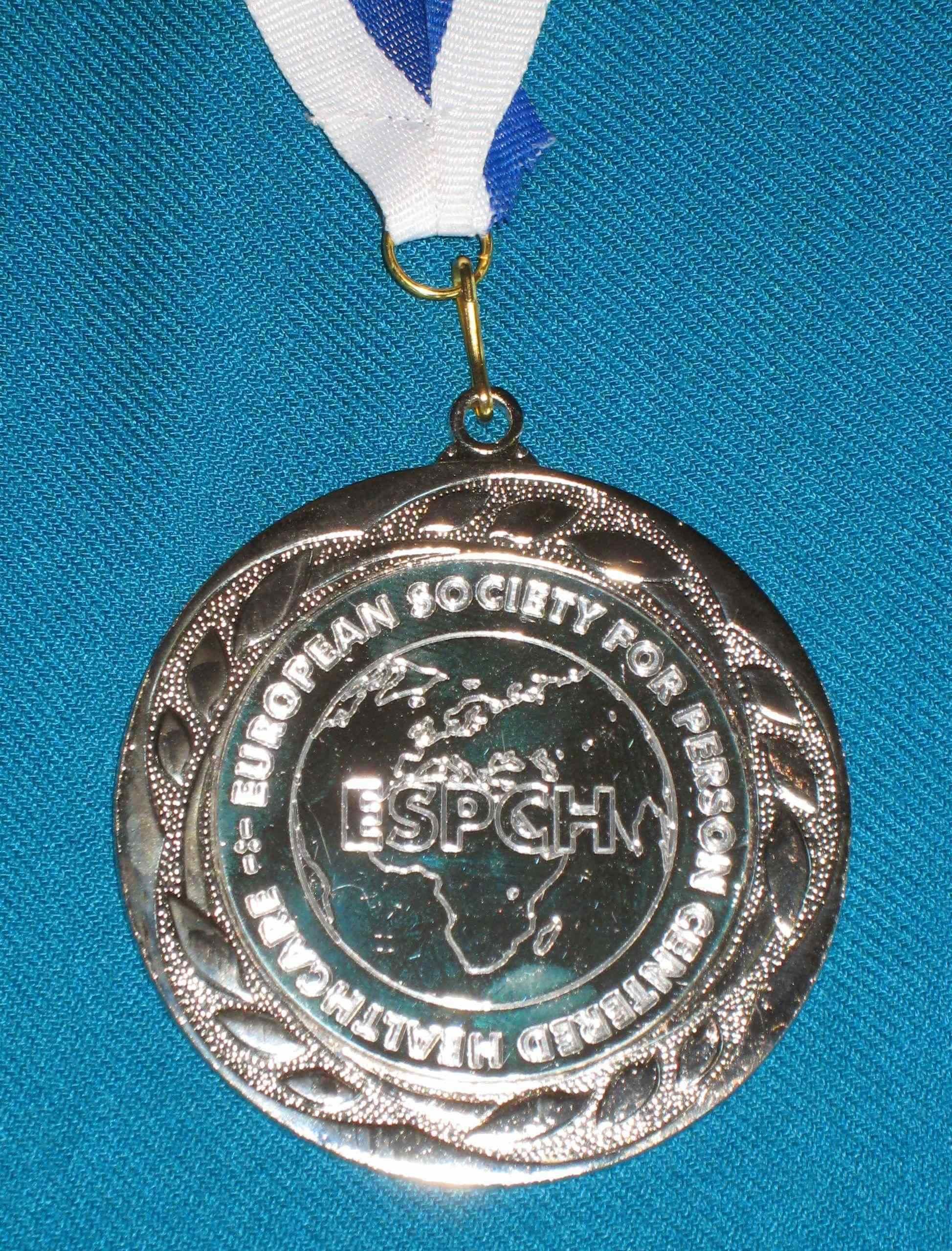 Eine silberne Medaille, in der Mitte das Logo ESPCH und die Umrisse von Europa und Asien, rundherum die Schrift: European Society for Person Centered Healthcare